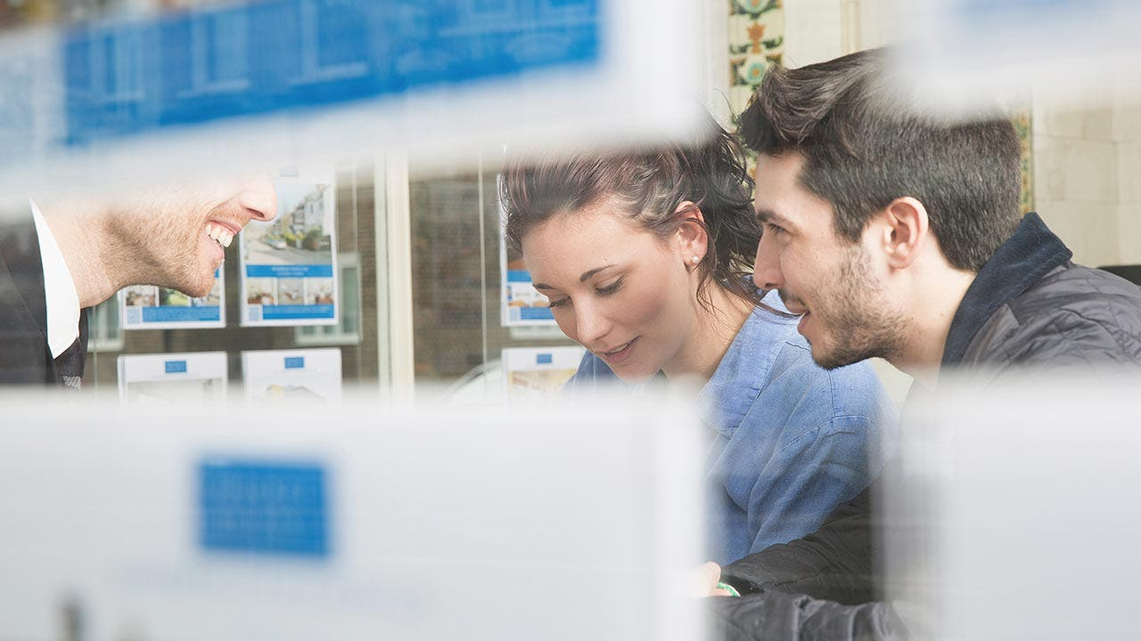 Couple looking at listings with a real estate agent
