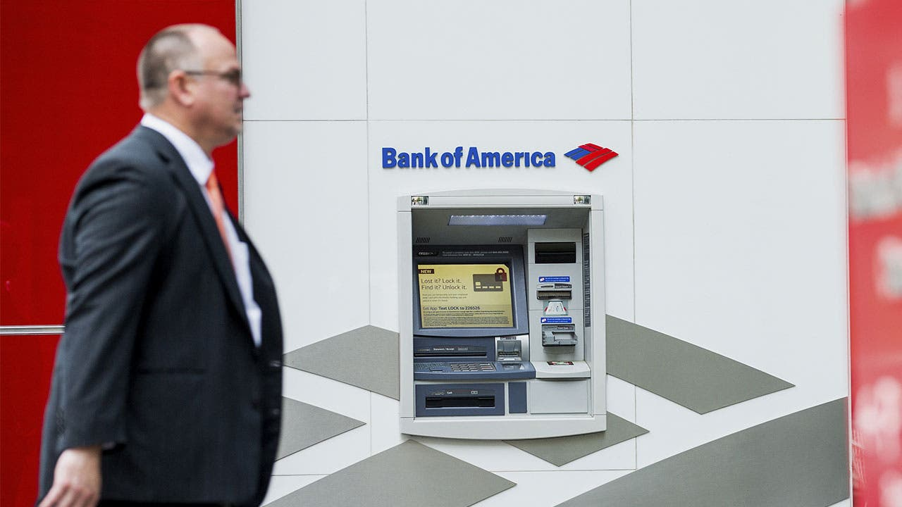 Man in suit walking past Bank of America ATM