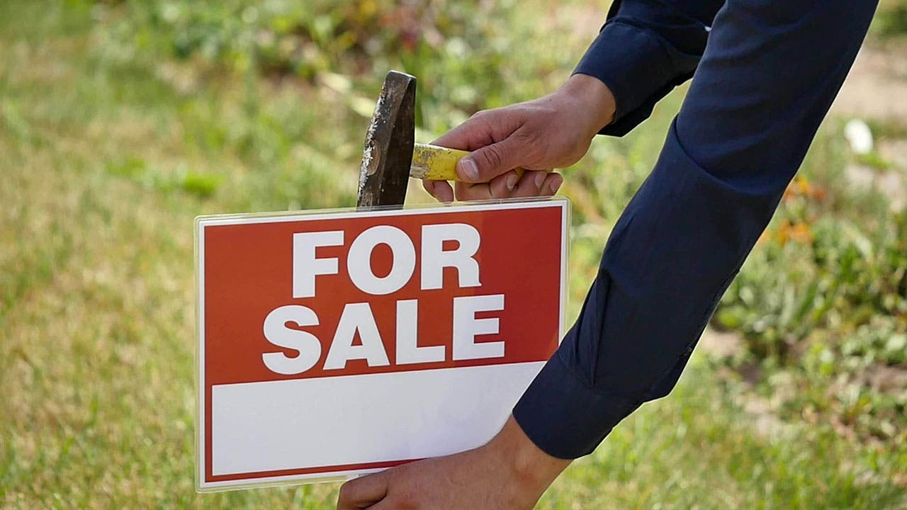 Person putting up for-sale sign