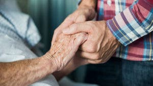 Adult child holding hands of elderly parent