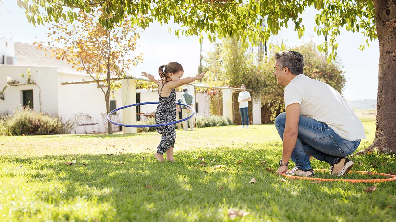 Dad and daughter playing with hula hoop