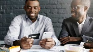 Two men at dinner and one paying with credit card