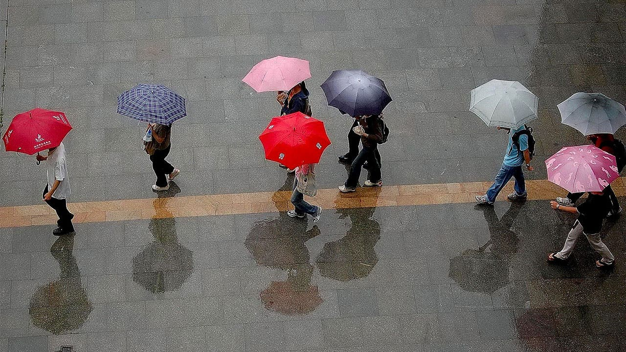 people walking through the rain with umberellas