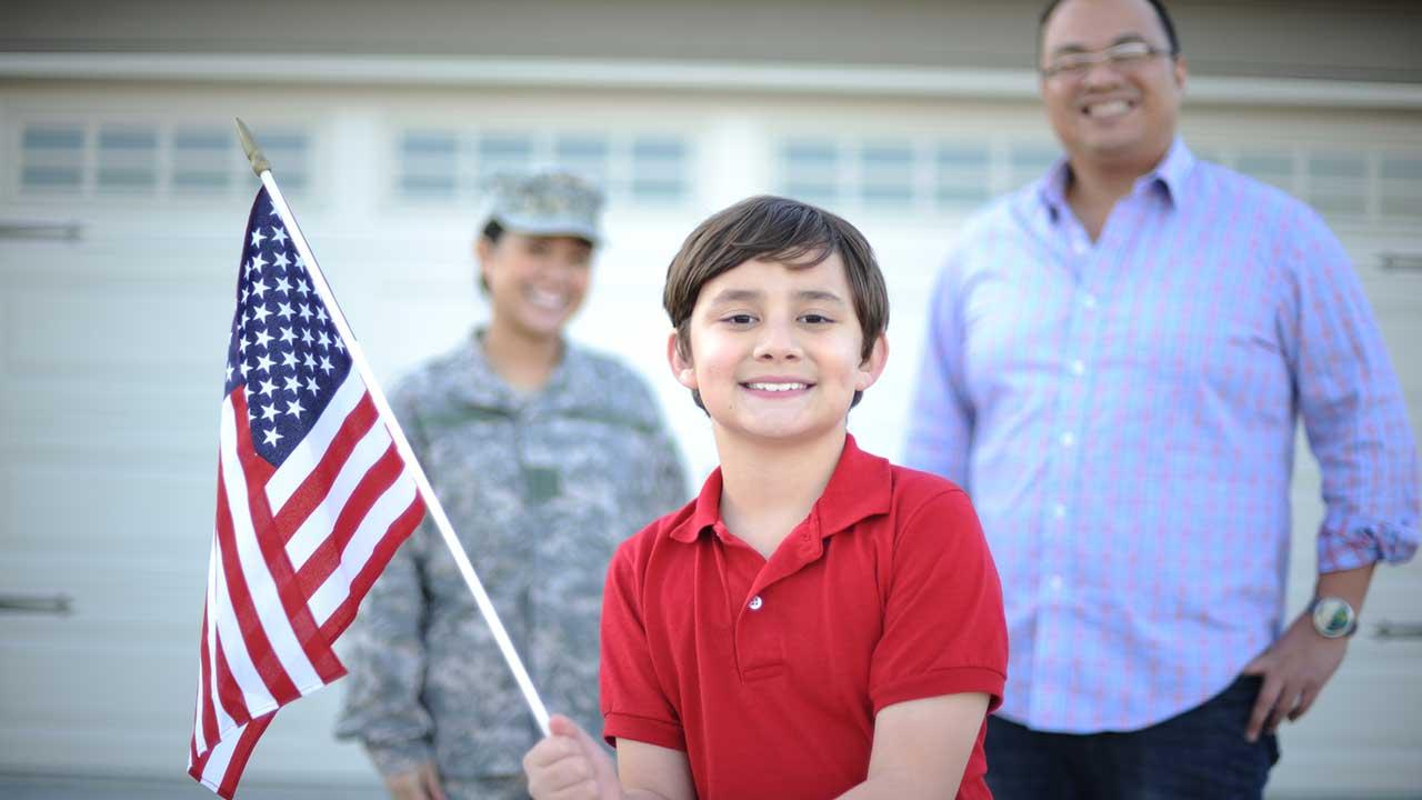 Boy holding U.S. flag, parents in background