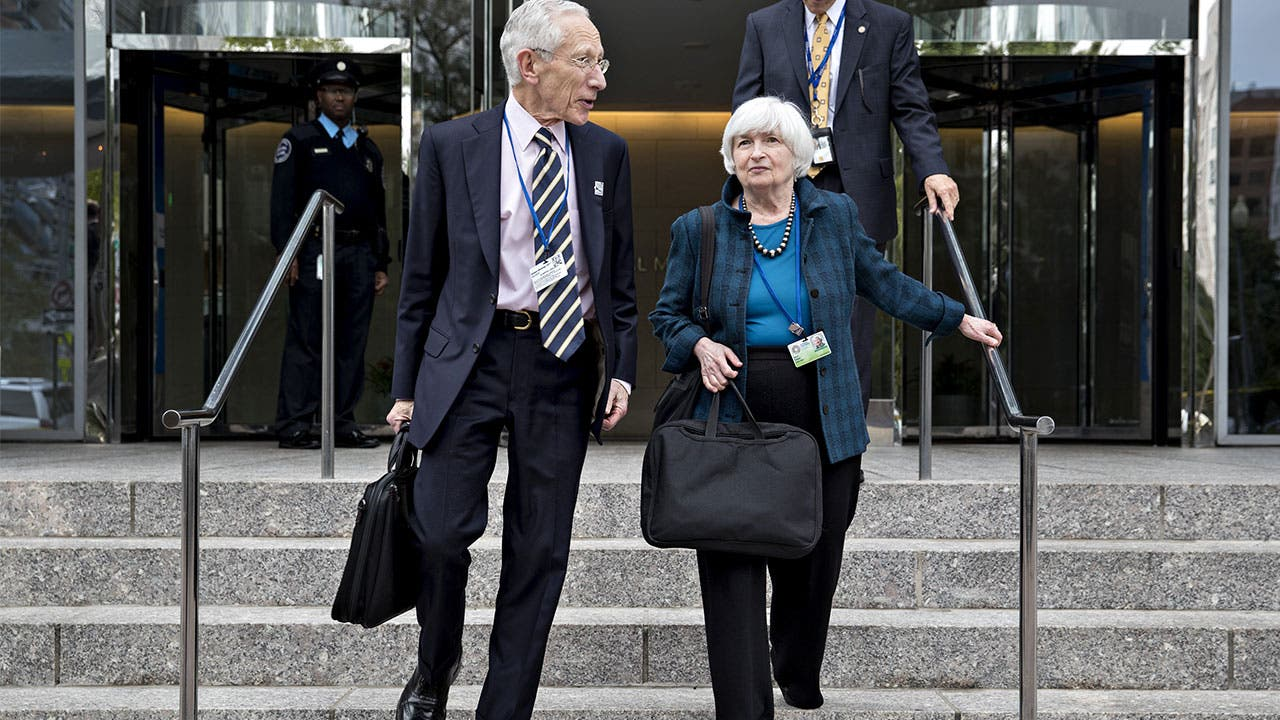 Janet Yellen, chair of the U.S. Federal Reserve, right, and Stanley Fischer, former vice chairman of the U.S. Federal Reserve, walk out of the International Monetary Fund