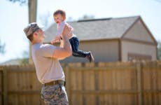 Man in military uniform playing with his young child