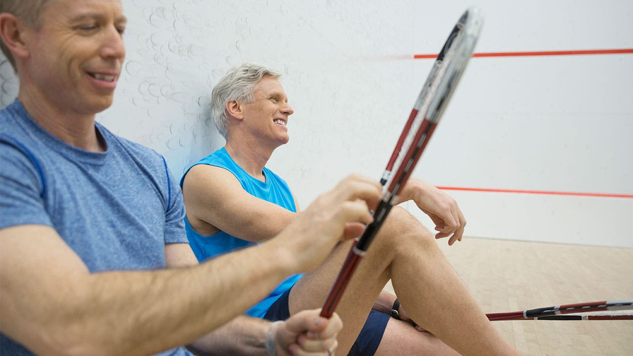 Two older men sitting after playing racquetball