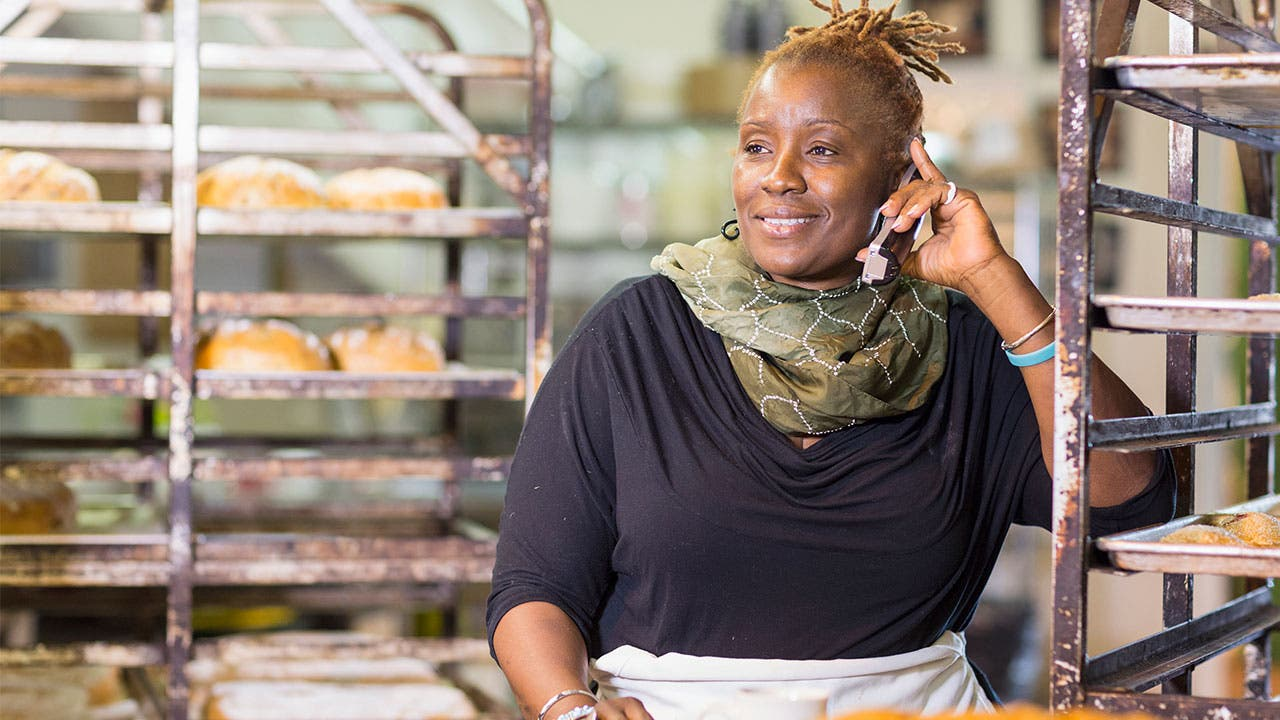 Woman working at bakery and talking on phone