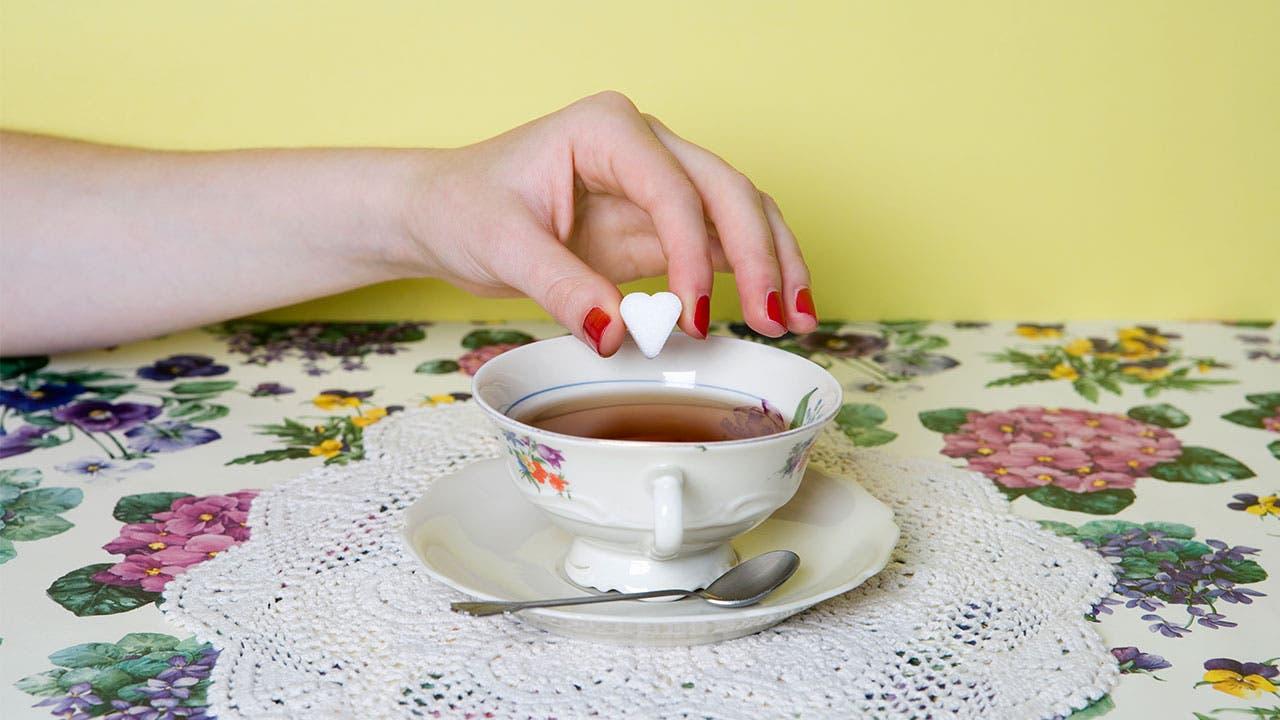 Woman dropping sugar cube into tea