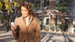 Woman walking outside looking at phone