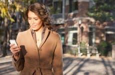 Woman walking outside looking at phone