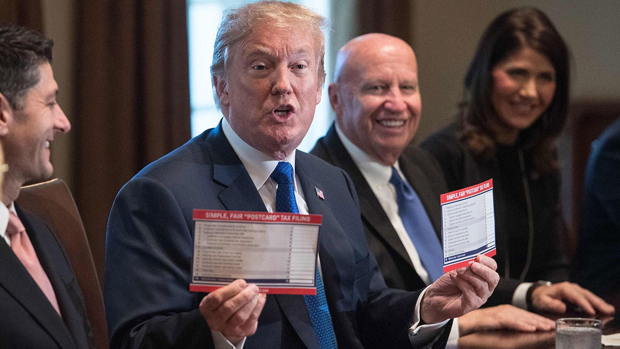 US President Donald Trump shows samples of the proposed new tax form as he meets with House Republican leaders and Republican members of the House Ways and Means Committee at the White House in Washington, DC, on November 2, 2017.