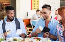 Young friends both try to pay for lunch with cash and credit card