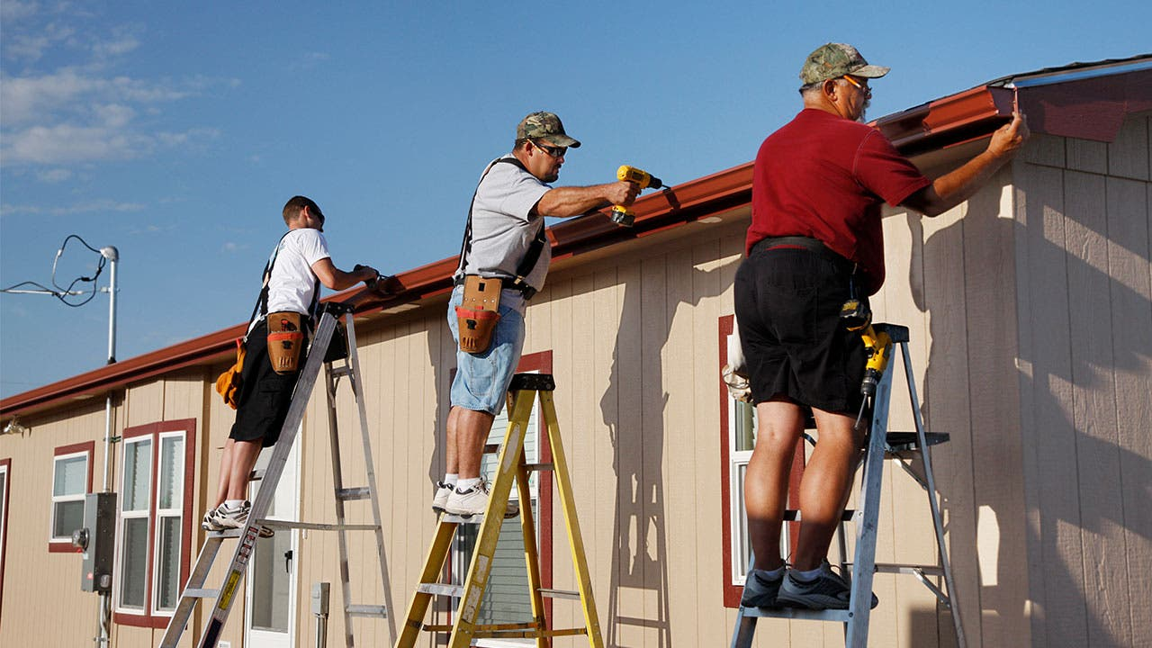 Three workers installing gutters
