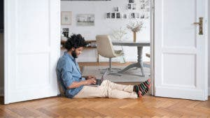 Man sitting on floor and using laptop