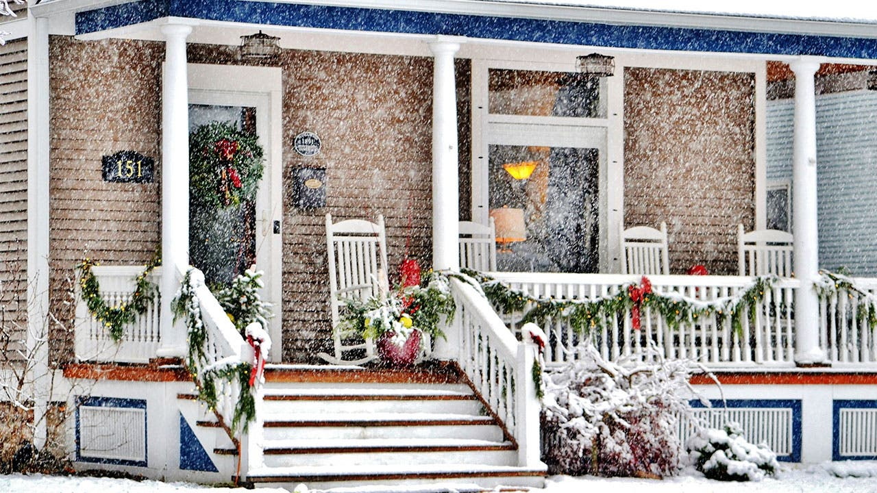 Snow falling on porch decorated for the holidays.
