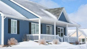 Blue house with snow on roof