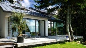 Sunlit backyard of home with glass doors
