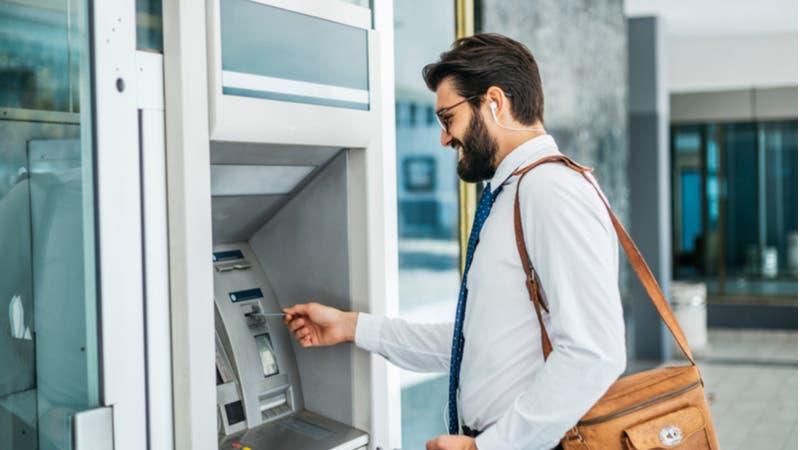 Bearded businessman using ATM