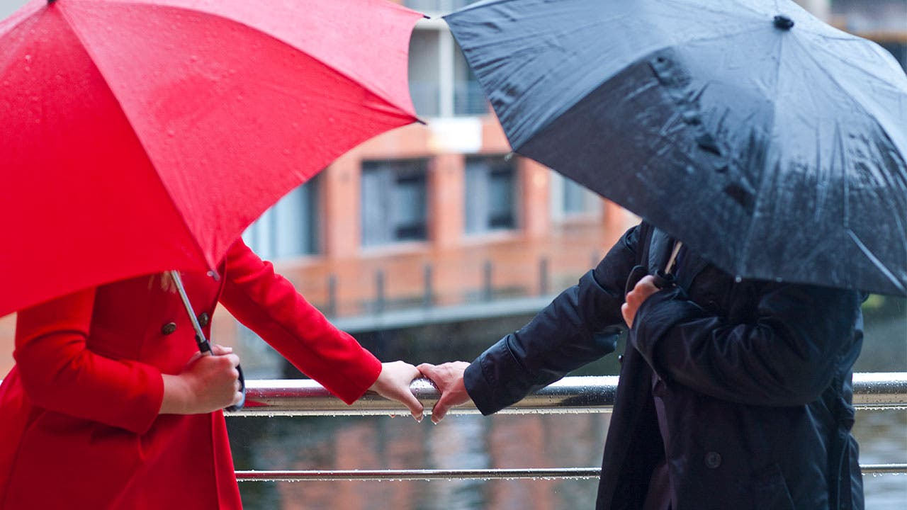 Man and woman with umbrellas touch