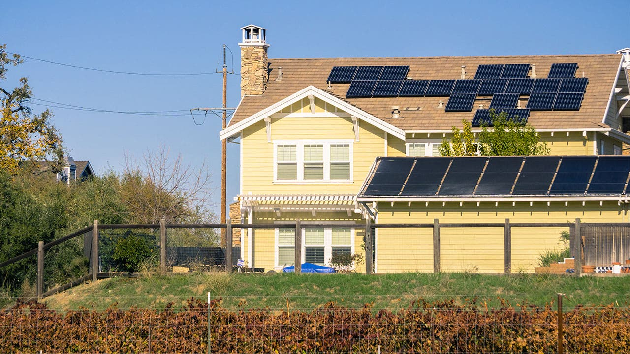 Yellow house with solar panels on roof
