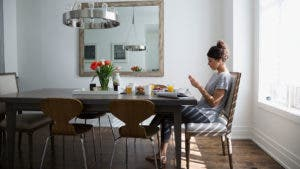 Woman at kitchen table looking at phone