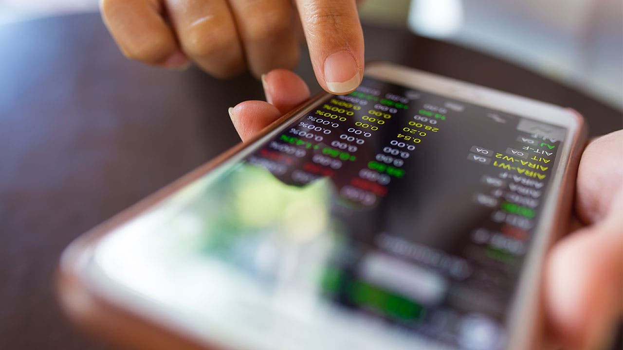 Woman using a financial app to check stocks