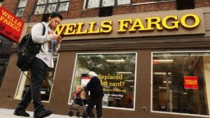 Pedestrians walking past a Wells Fargo branch