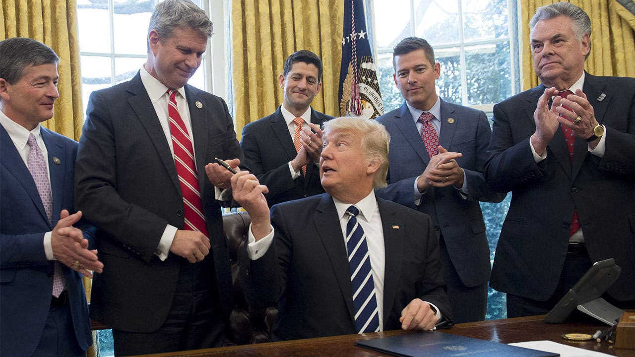 Donald Trump with a pen after signing piece of legislation