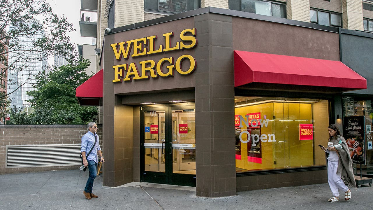 Man and woman walking past Wells Fargo in Manhattan