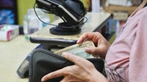 Woman taking a $10 bill out of her wallet