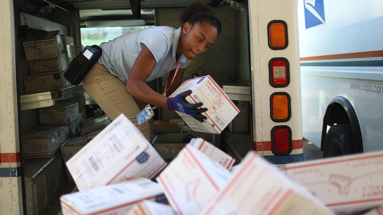USPS mail worker unloading packages from mail truck
