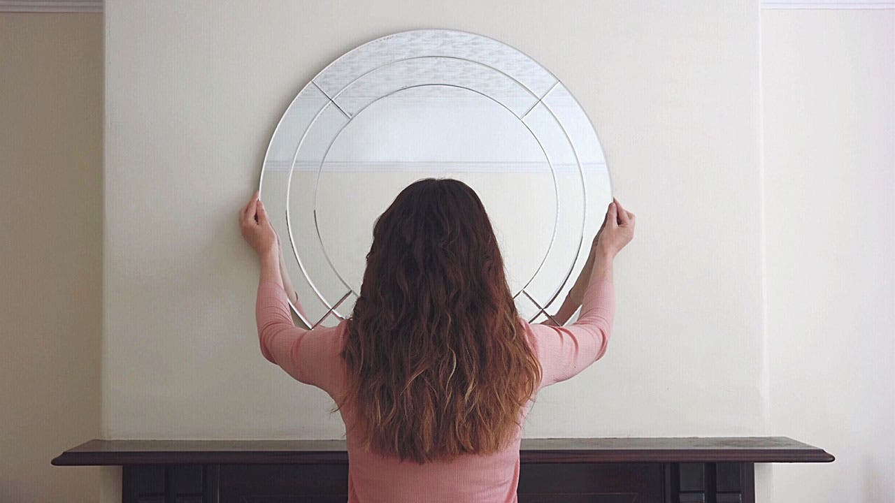 Woman places mirror on wall