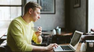 Man on computer drinking tea
