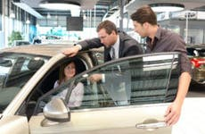 Car salesman showing a car to couple