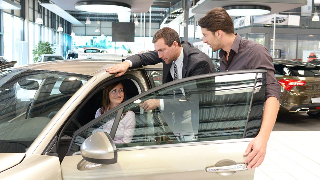 Car salesman showing a car to couple
