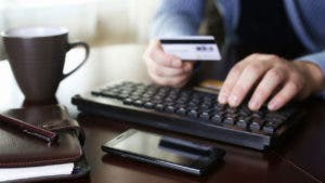 Man typing in credit card purchase on keyboard