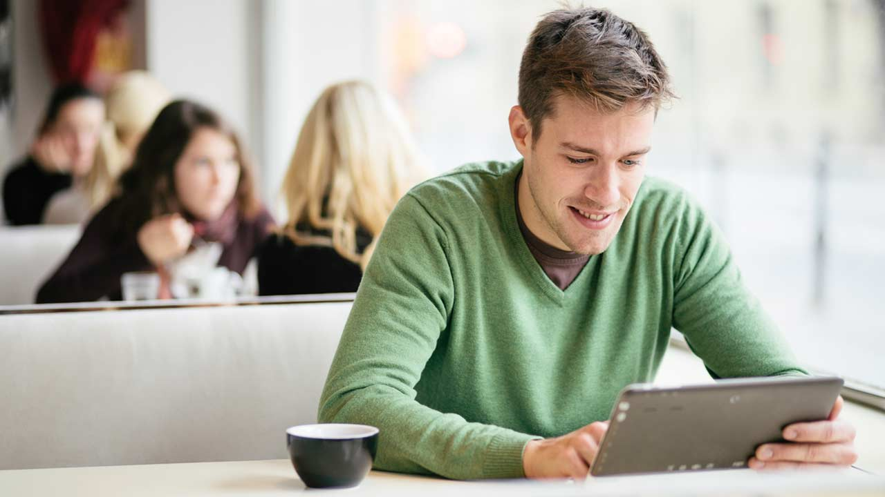 Young man wearing green jumper using tablet computer in cafe