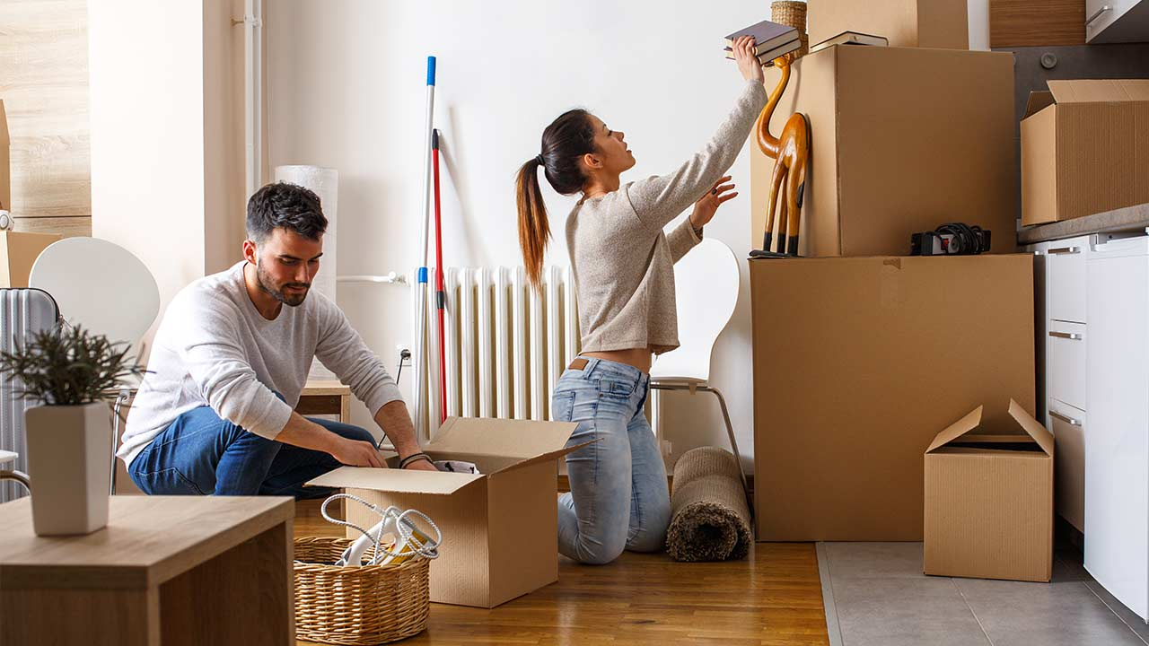 Young couple unpacking cardboard boxes at new home Moving house Real estate