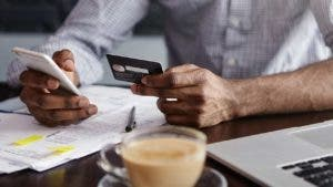 Close up shot of African man's hands holding mobile and credit card. Dark-skinned businessman checking account balance, using online banking application on his cell phone, drinking coffee at cafe