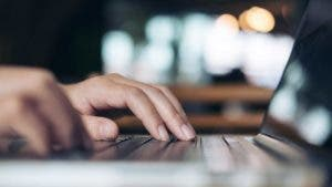 Closeup image of a business woman's hands working and typing on laptop keyboard in office