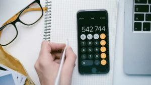 iPhone calculator on notepad with person holding pen and glasses