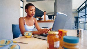 Woman using laptop at kitchen table