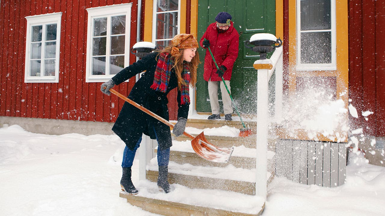 Mother and daughter shoveling snow on front steps