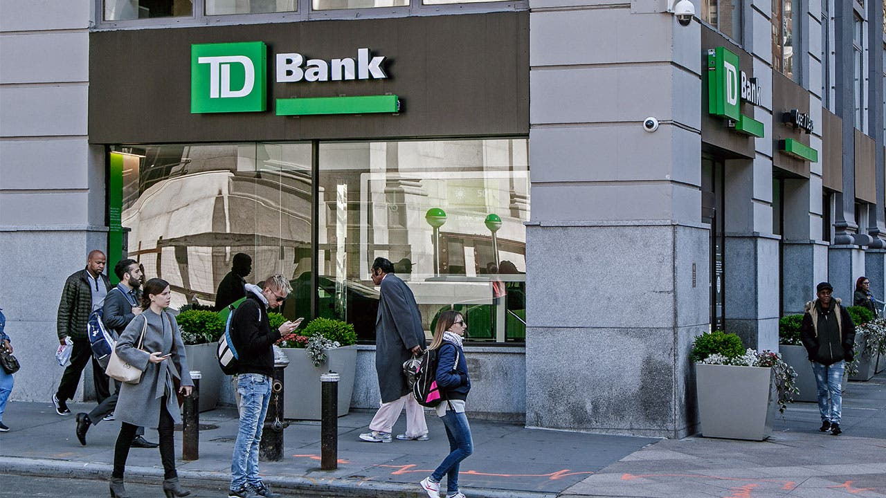 TD Bank branch with people walking past the bank
