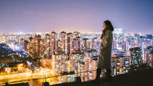 Woman overlooking cityscape at night