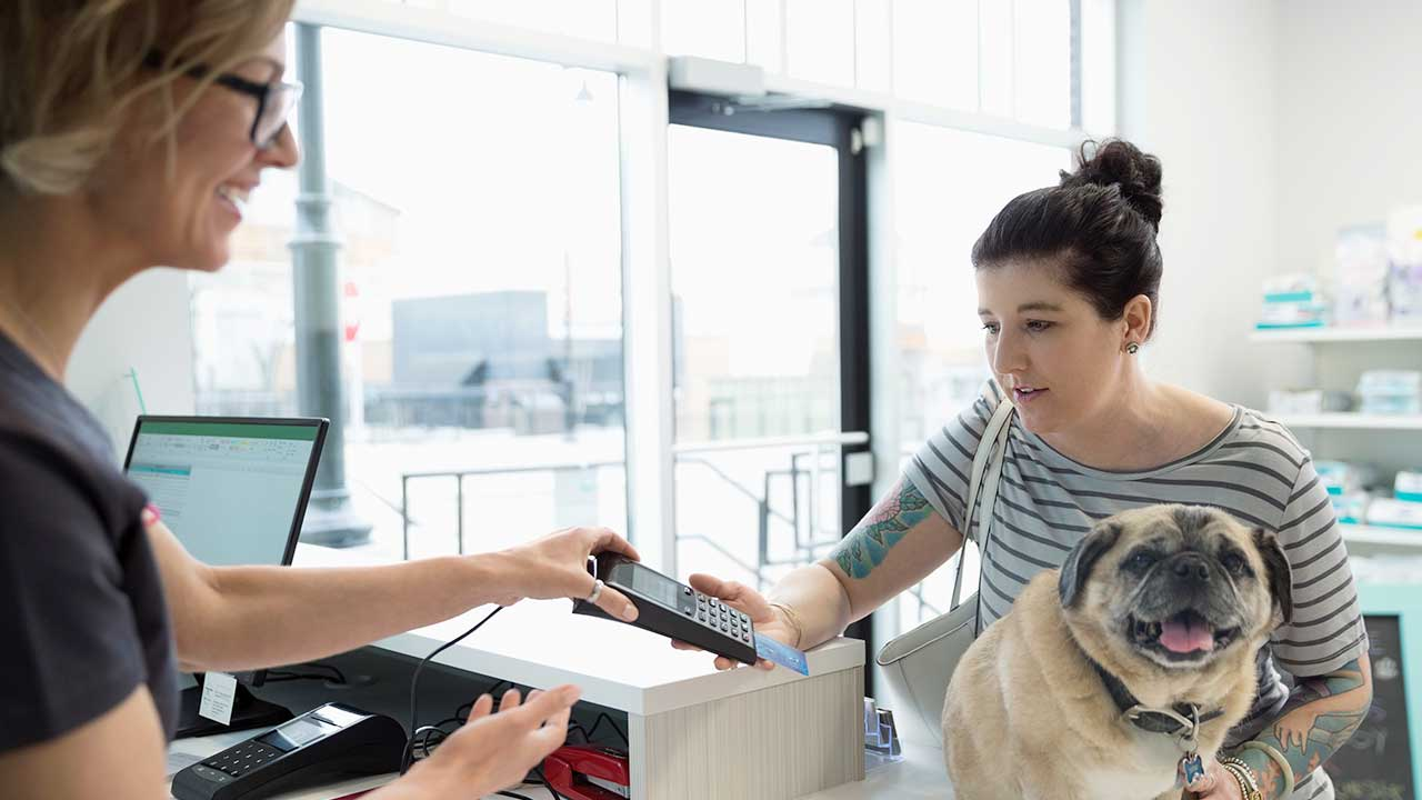 Woman paying with card in vet's office