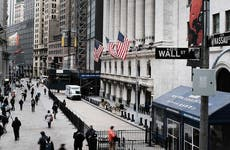 People walk by the New York Stock Exchange (NYSE) before the Opening Bell.