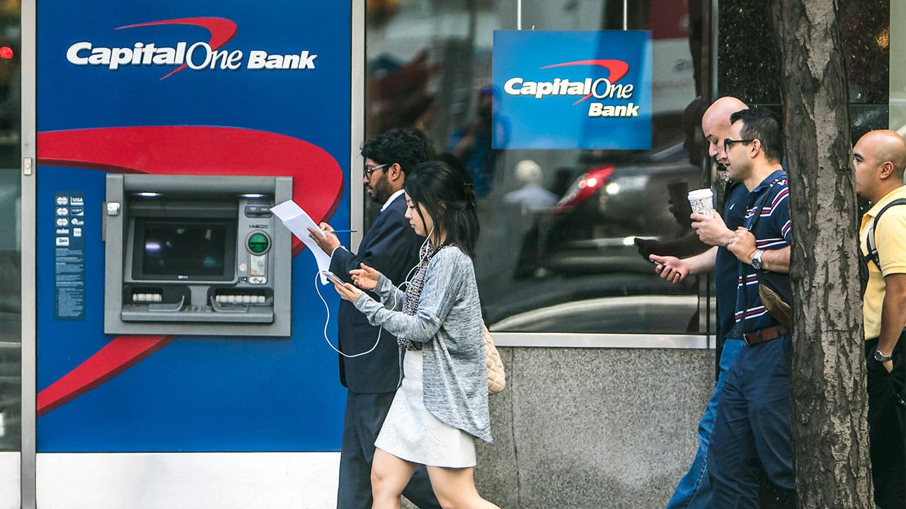 People walking past a Capital One bank