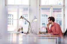 Man sits at his desk looking at computer